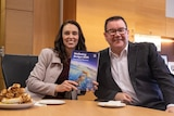Jacinda Ardern is seated and holding up a paper copy of the 2021 budget, minister grant robertson next to her, both smiling