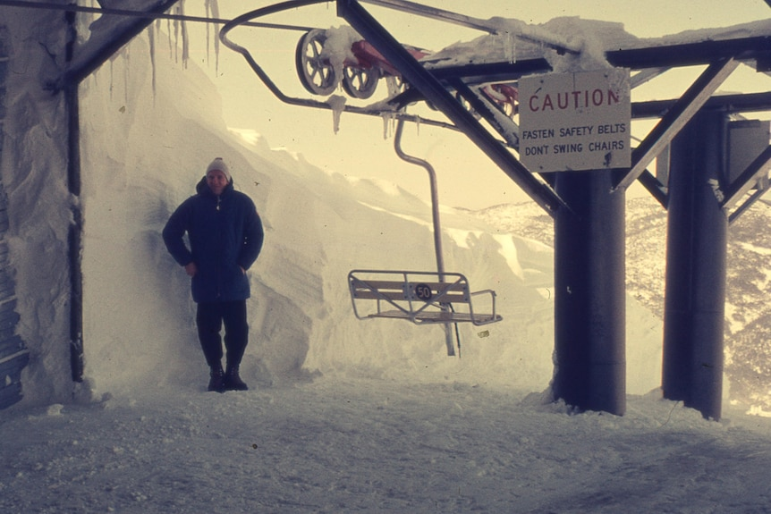 Person in snow gear stands by ski chair lift in many metres of snow