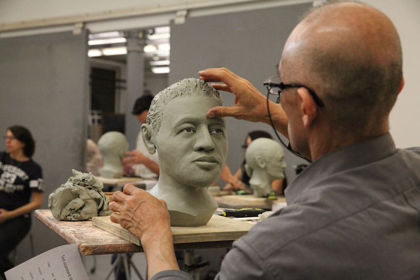 A student works on a sculpture of a human face.