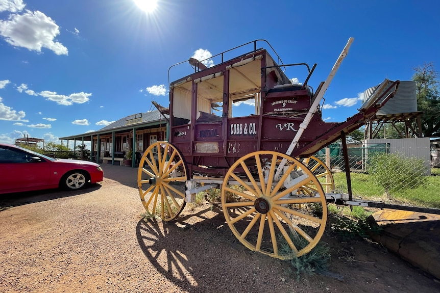 An old red wooden carriage with white wheels sits in the sun in front of an old outback pub.
