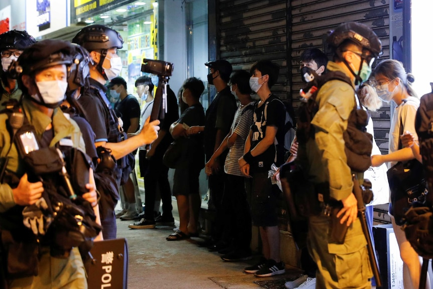 Riot police wearing masks line protesters up against a wall.