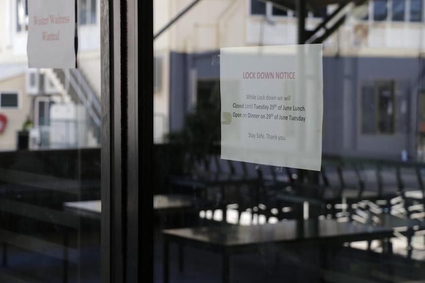A lockdown notice is seen stuck to a shop window.