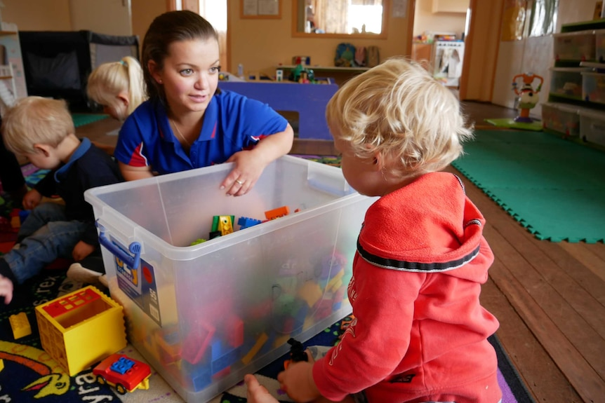 A female childcare worker plays with children and toys in a centre.