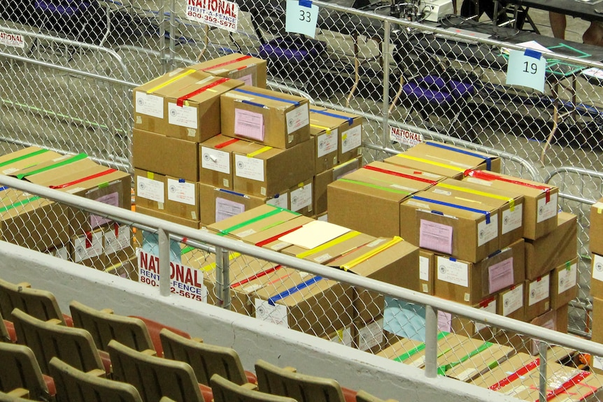 cardboard boxes with colorful tape sit behind a chain-link fence