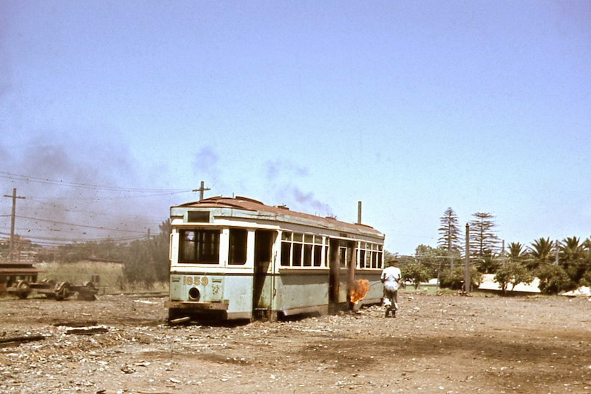 A man walks toward an old tram with a flame