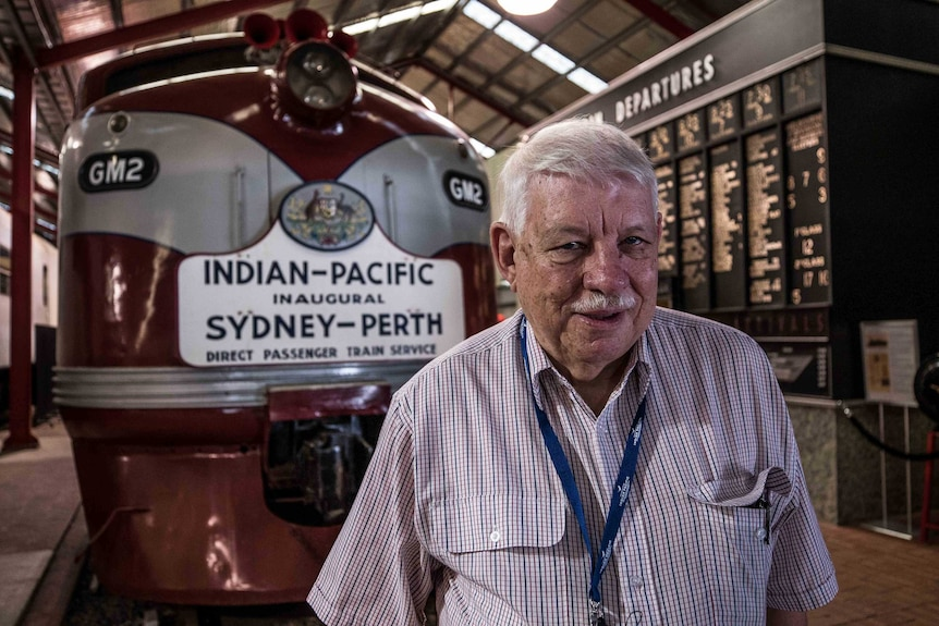 Man standing in front of old train locomotive