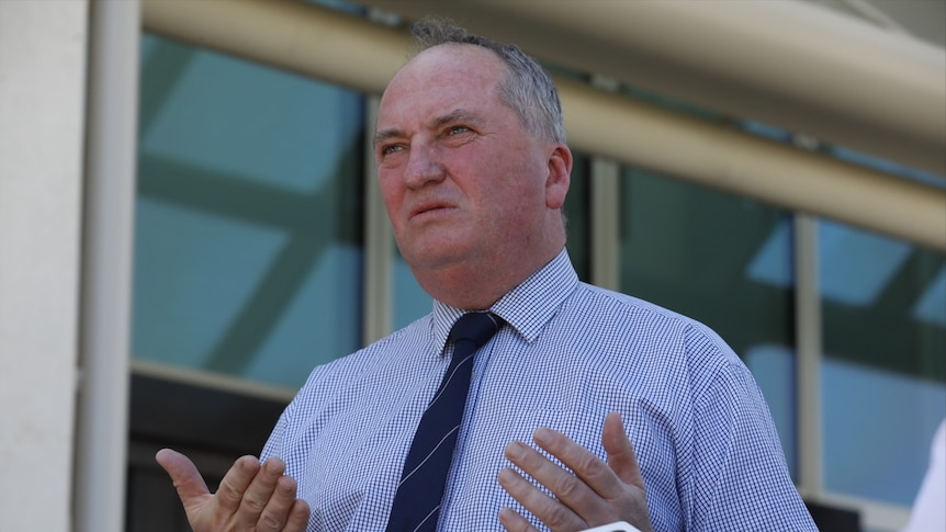 Barnaby Joyce in a shirt and a dark tie looks to the left of camera with his lips pursed and his palms facing upwards