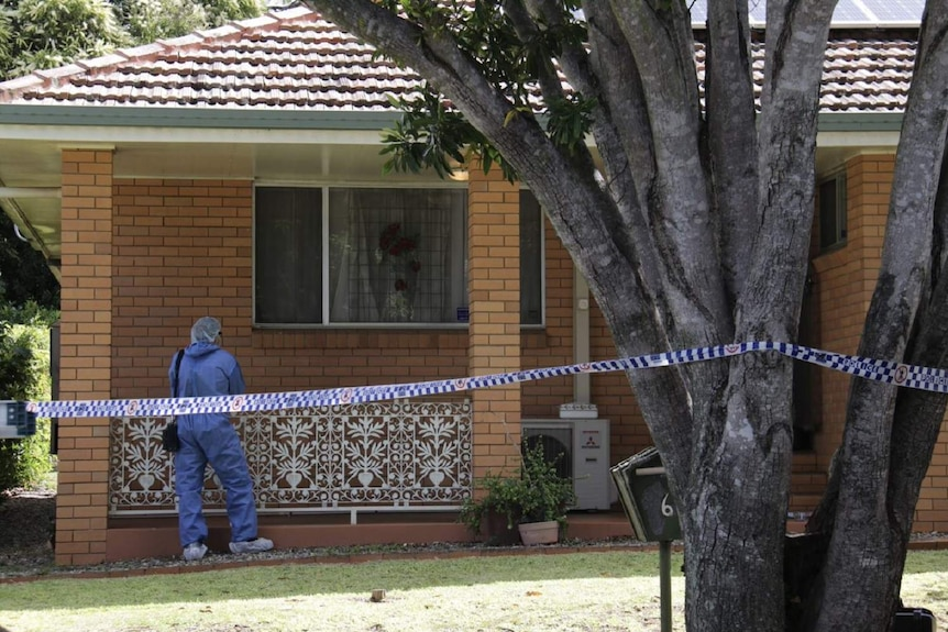 A forensic investigator at a house with police tape across the front yard.