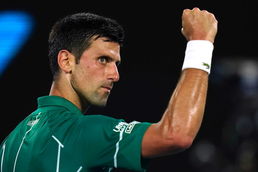 A tennis player pumps his fist as he looks at he crowd after a winning point.