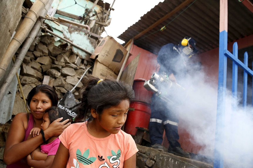 A health worker fumigates a house as residents wait outside during a campaign against the Zika virus.
