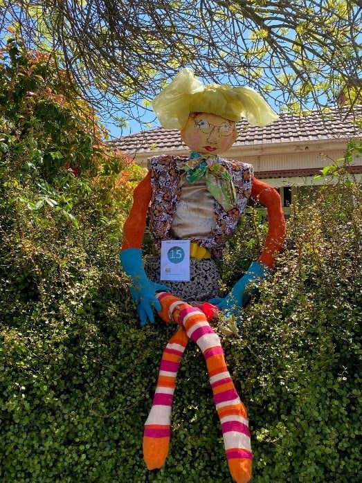 A lady scarecrow with brightly colourd clothes and hair sits on top of a hedge.