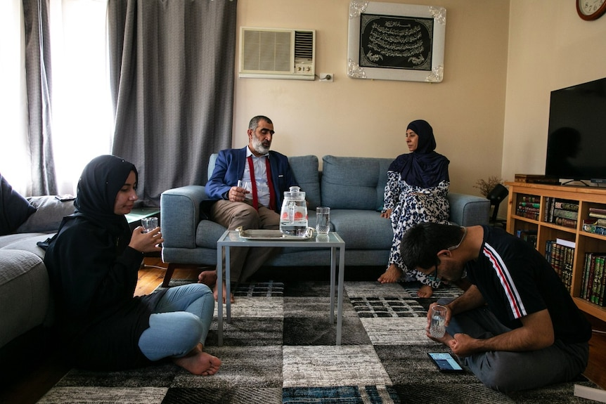 Four people sitting in a living room.