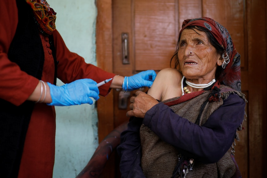 An Indian woman holds down her sleeve as the hands of a health worker wearing blue gloves administers her vaccine.