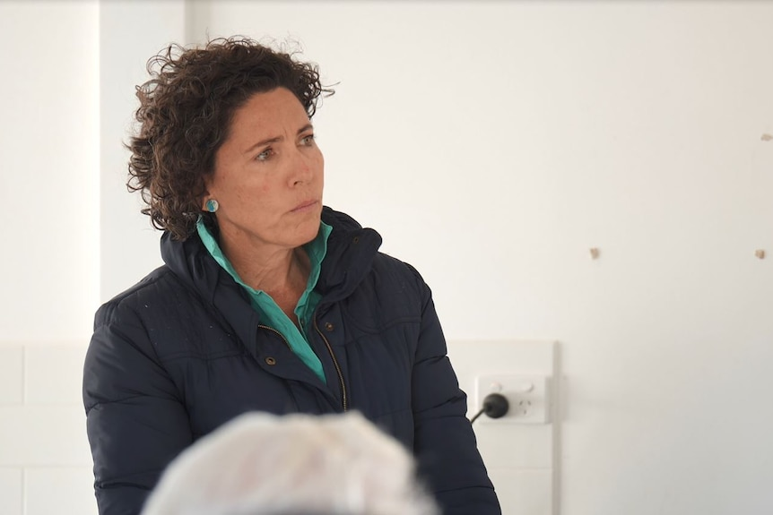 Woman listens at a community meeting