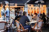 Diners wear protective face masks at a cafe in Melbourne CBD
