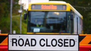 a 'road closed' sign attached to red barricades, a yellow school bus approaches the closure