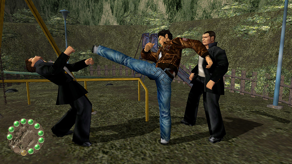 In a scene from a video game, a Japanese man in jeans and brown jacket kicks and fights two me in black in park-like setting.