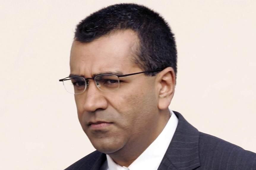 You view a portrait image of Martin Bashir in a dark suit, navy tie walking in front of a beige background.