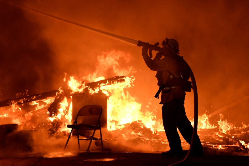 A firefighter sprays water into the flames.