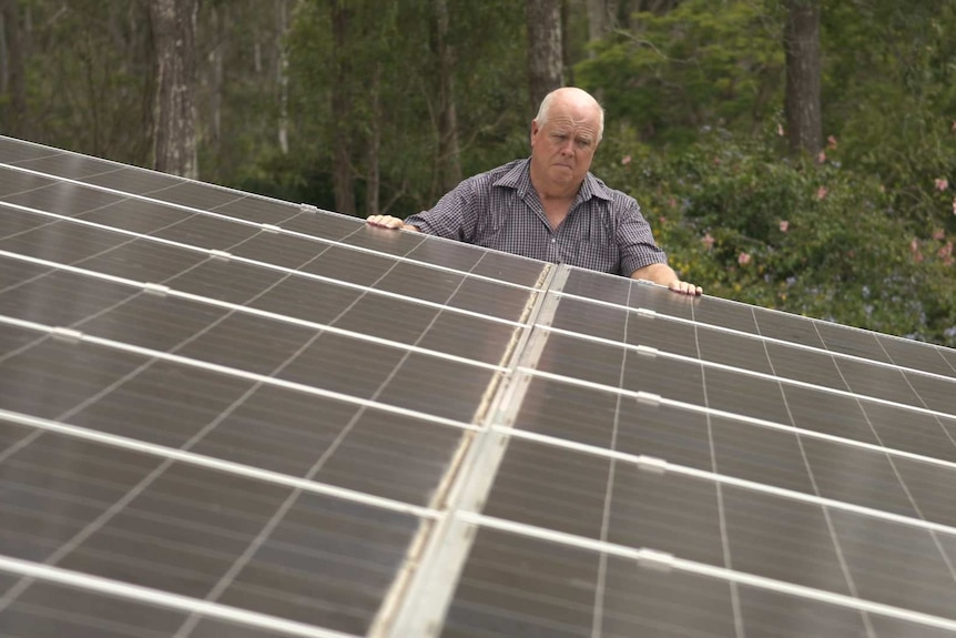 Alex Smith stands on a ladder with his hands on solar panels.