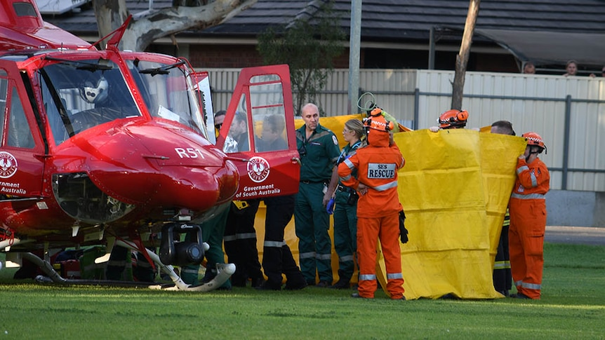 Emergency service personnel stand around medical helicopter
