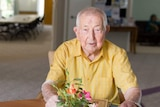 An elderly man sits at a table in a dining room.