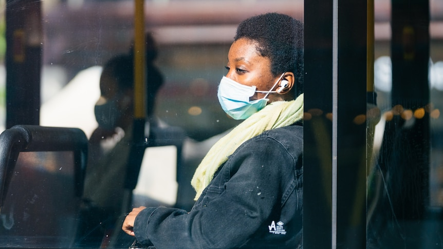 A young women wearing a face mask looks out of a window on board a Transperth bus within the CBD.