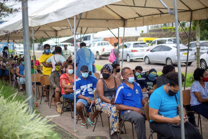 Fijians sit in a line of chairs under a tarpaulin as they wait to receive a dose of the AstraZeneca vaccine