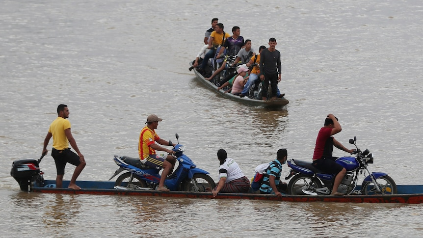 People cross a river in two boats.
