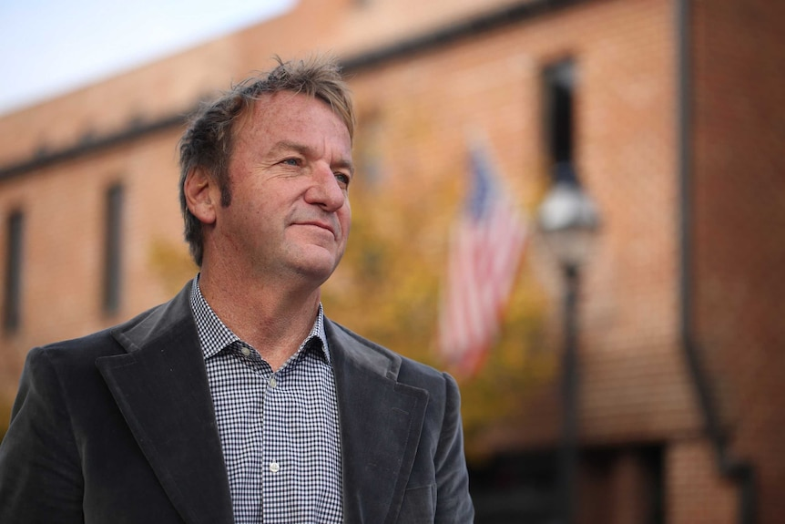 Close up  of Gavin Buckley, who has been elected mayor of Maryland's capital Annapolis, in the street with US flag in background