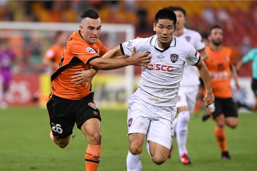 Roar player Nicholas D'Agostino (left) competes with Muangthong United player Aoyama Naoaki.