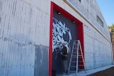 Port Adelaide artist Kab101 brush-paints the door of a warehouse on Mundy Street.