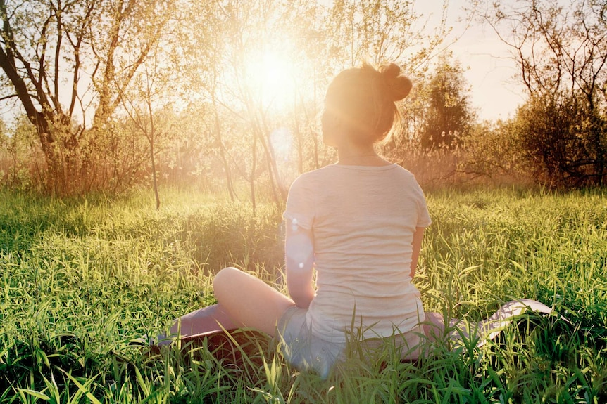 Woman sitting in the grass in a field with the sun low on the horizon