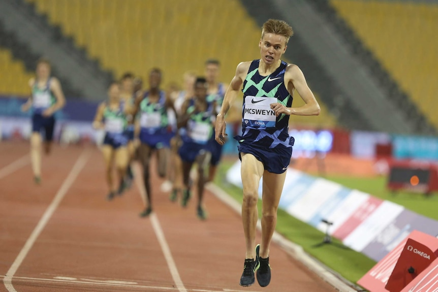 An athlete crosses the line, with the chasing pack well in the background.