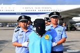 Chinese police stand with deported fraud suspects on the tarmac. The suspects are hooded and wearing numbered blue vests.