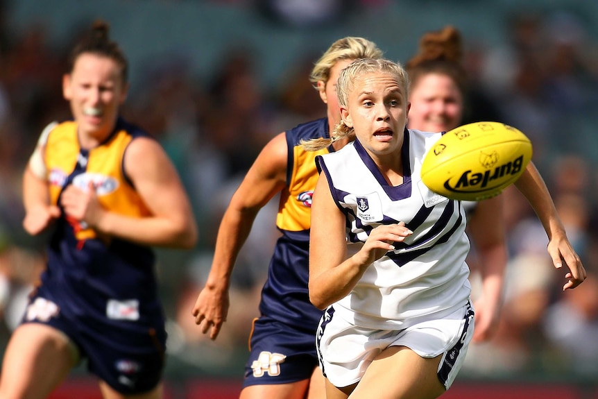 Fremantle Dockers player Courtney Ugle chases a loose yellow football as she is chased by two West Coast Eagles players.