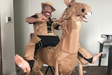 A man in a paper cowboy costume rides a horse constructed from various materials.