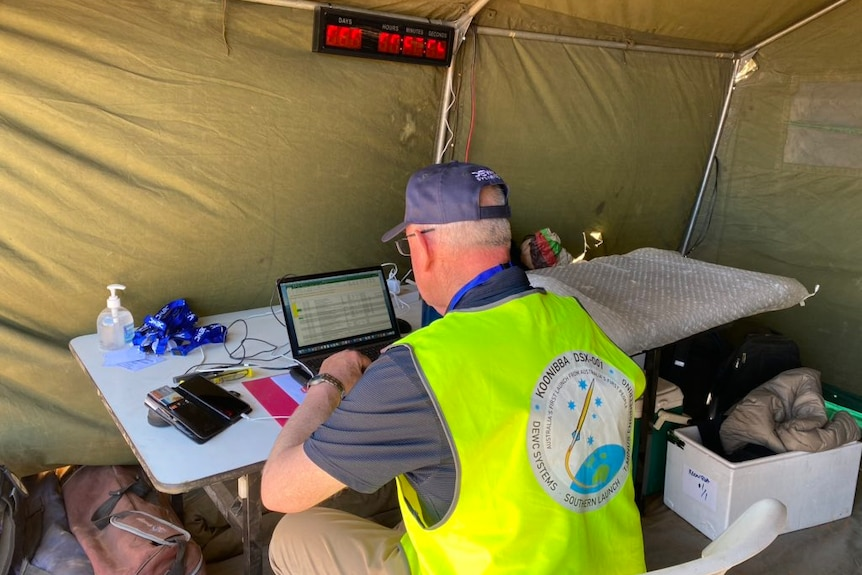 A man looks at a laptop computer in a tent
