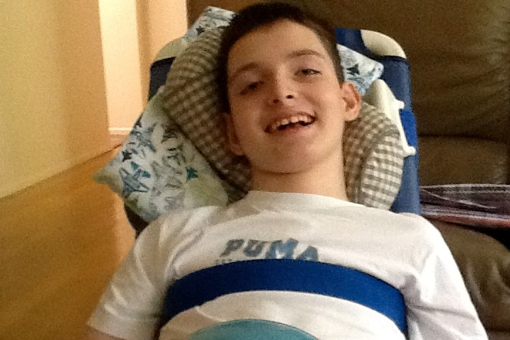 Harrison Creevey smiles at the camera reclining in chair.