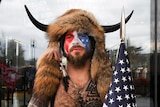Jacob Chansley looks into the camera as he wears horns and a fur hat with face paint on.