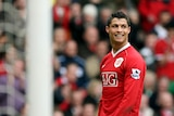 Cristiano Ronaldo gives a big smile as he stands on the pitch at Old Trafford in his Manchester United kit during a game.