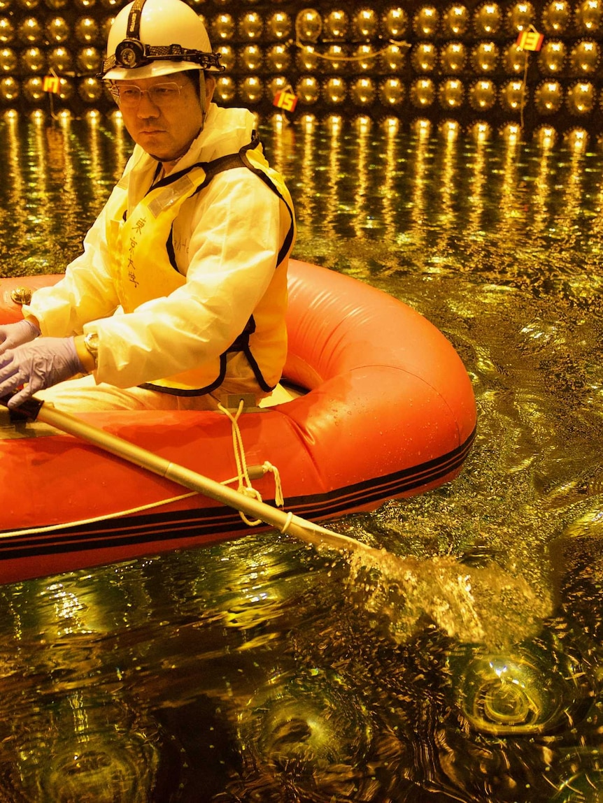 A Japanese scientist in a rubber boat in shallow water inside Super Kamiokande tank
