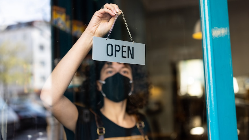 A young non-binary person hanging an open sign from the door of a small bakery.