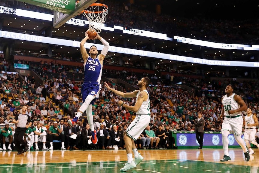 a male basketballer player jumps high to put ball in basket