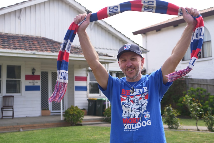 Shannon Yates stands in his front yard in a Bulldogs top, holding a team scarf in the air, in front on his painted house