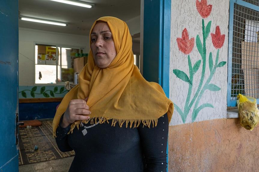 Una mujer musulmana que lleva un pañuelo amarillo parece contemplativa mientras se encuentra en la entrada de un aula