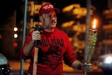 A supporter of US President Donald Trump holds a tiki torch and a pitchfork during a protest.