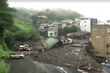 Crushed houses sit atop large piles of mud and debris