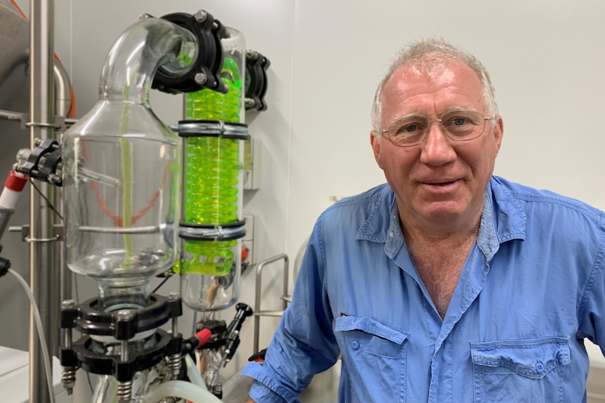 Man in blue shirt posing beside a green glass scientific tube in a lab.