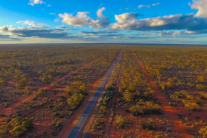 An aerial shot of a remote area, with a lone road running through scrubland.